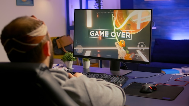 Koniec gry dla zdenerwowanych graczy grających na potężnej komputerowej strzelance fps podczas turnieju online. pokonany mężczyzna ze słuchawkami przesyłający strumieniowo cybernetykę online, występujący późno w nocy w pokoju gier
