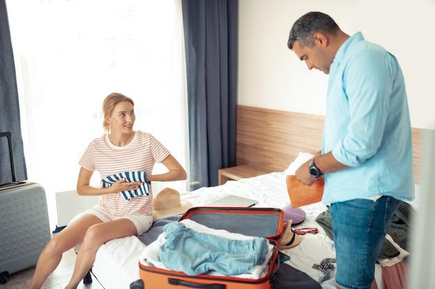 Koniec wakacji. skoncentrowany mąż i żona pakują razem walizkę podróżną na hotelowe łóżko.