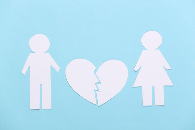 Koniec związku, rozwód. podziel papierowego mężczyznę i kobietę, złamane serce na niebiesko