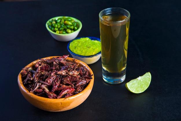 Koniki polne chapulines i tequila. tradycyjne meksykańskie jedzenie