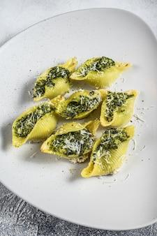 Konkiloni jumbo muszle makaron conchiglioni faszerowany szpinakiem na talerzu na białym stole. widok z góry.