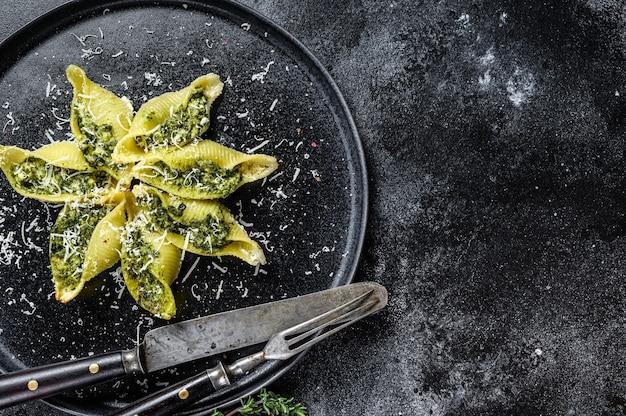 Konkiloni włoski makaron jumbo muszle conchiglioni faszerowany mięsem wołowym i szpinakiem na talerzu na czarnym stole. widok z góry.