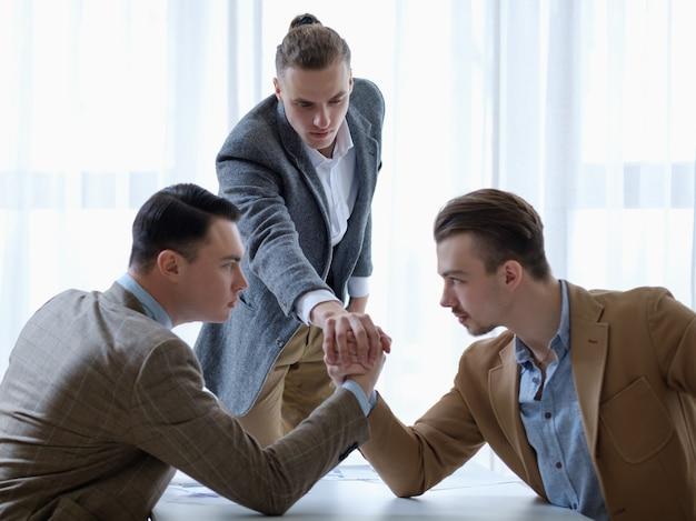 Konkurencja biznesowa. młody mężczyzna sędziowanie dwóch rywali w walce siłowania się na rękę.