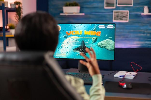 Konkurencyjny afrykański gracz świętujący zwycięstwo w e-sporcie w domu. konkurencyjny gracz używający joysticka do mistrzostw online siedzący na fotelu do gier późno w nocy