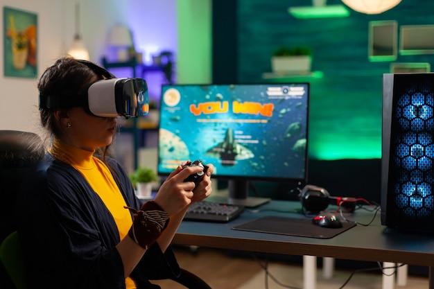 Konkurencyjny gracz patrzący na potężny komputer, grający w strzelankę online późno w nocy z zestawem słuchawkowym vr i bezprzewodową konsolą. wirtualne cyberprzesyłanie strumieniowe online podczas turnieju gry