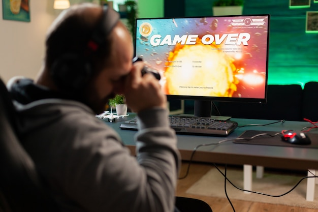 Konkurencyjny gracz przegrywający mistrzostwa e-sportowe za pomocą technologii bezprzewodowej sieci pokonany mężczyzna grający w kosmiczną strzelankę online z potężnym profesjonalnym komputerem trzymającym kontroler