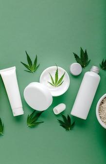 Konopny krem nawilżający w białym słoiku z liśćmi konopi olej cbd i zestaw kosmetyków do pielęgnacji skóry w białych butelkach tubkach na zielonym tle.
