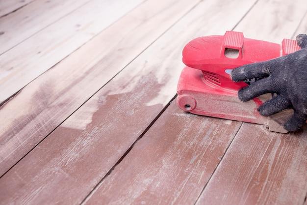 Konserwacja polerowania podłóg drewnianych przez szlifierkę.