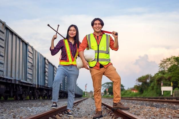 Konserwator w kombinezonie ochronnym stoi obok pociągu towarowego z kluczem. w branży transportu kolejowego pracują azjatyccy robotnicy. koncepcja inżyniera i naprawy. bezpieczeństwo przede wszystkim