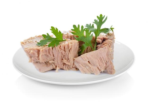 Konserwować tuńczyk ryba w talerzu na biel przestrzeni