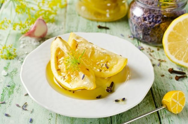 Konserwowane cytryny z solonym czosnkiem lawendowym i goździkami na drewnianym stole i przyprawami