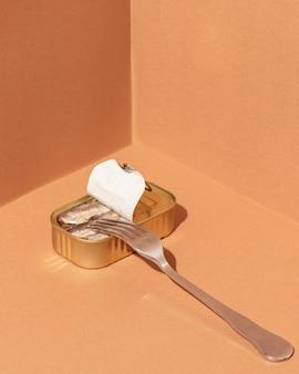 Konserwowane sardynki w dużym kącie w puszce z widelcem
