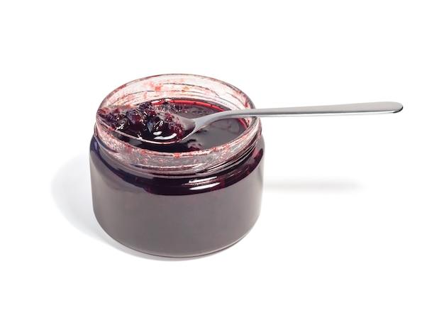 Konserwuj lub konfituj z czerwonymi jagodami w przezroczystym szklanym słoju i srebrnej łyżeczce.