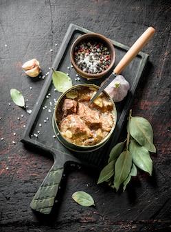 Konserwy mięsne w puszce na desce do krojenia. na ciemnej rustykalnej powierzchni