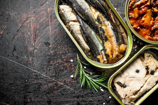Konserwy rybne w puszkach rozmarynu na ciemnym rustykalnym stole.