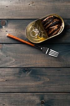 Konserwy rybne w sosie konserwują na ciemnym drewnianym stole