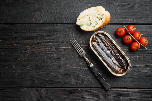 Konserwy rybne w zestawie olejowym, na tle czarnego drewnianego stołu, płaski widok z góry, z miejscem na kopię tekstu