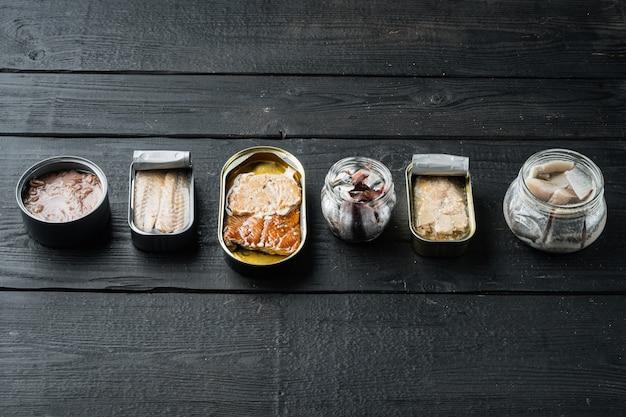 Konserwy rybne z różnymi rodzajami asortymentu zestaw owoców morza, na czarnym drewnianym stole