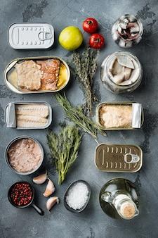 Konserwy rybne, zestaw topowych amerykańskich przetworów, na szarym stole z ziołami i dodatkami, widok z góry na płasko