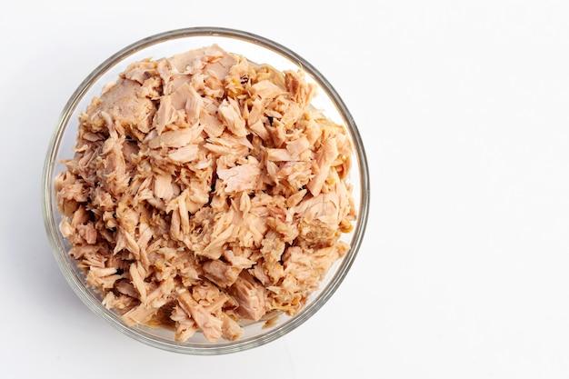 Konserwy tuńczyka w szklanej misce na białym tle.