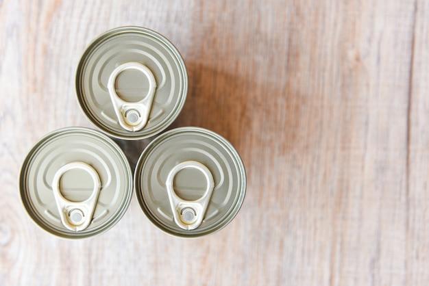 Konserwy w metalowych puszkach na drewnianym tle, widok z góry konserwy nietrwałe produkty do przechowywania żywności w kuchni w domu lub na datki