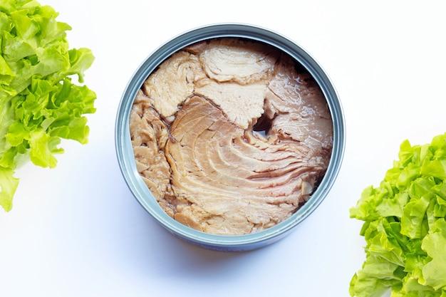 Konserwy z tuńczyka z zielonymi liśćmi dębu na białym tle
