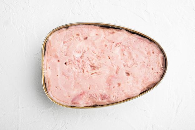 Konserwy, zestaw szynek mięsnych, na białym tle kamiennego stołu, widok z góry płaski lay