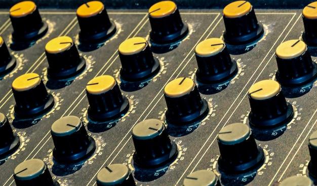 Konsola miksera dźwięku. biurko do miksowania dźwięku. panel sterowania miksera muzycznego w studio nagrań. konsola miksująca audio z suwakami i pokrętłem regulacyjnym. inżynier dźwięku. mikser dźwięku steruje transmisją radiową