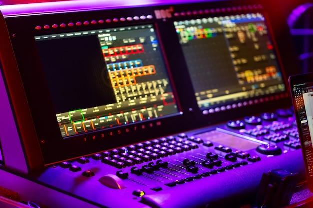 Konsola miksera dźwięku z przyciskami, suwakami i wyświetlaczami na koncercie.