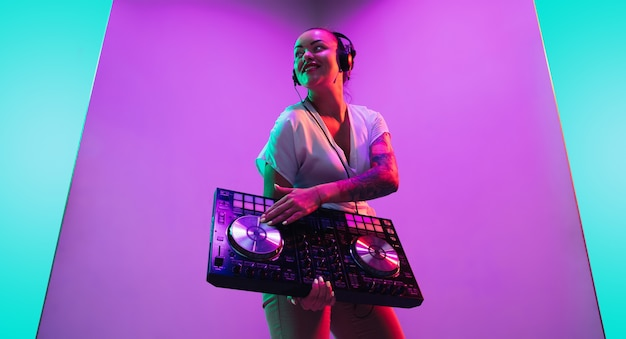 Konsola miksująca. młoda kobieta muzyk w słuchawkach wykonujących na fioletowym tle w świetle neonowym. pojęcie muzyki, hobby, festiwalu, rozrywki, emocji. radosny gospodarz imprezy, dj, portret artysty