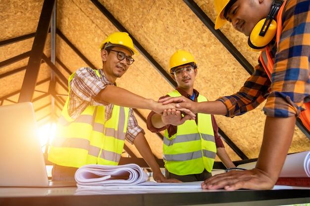[konstrukcja pracy zespołowej] zespół inżynierów i architektów łączy ręce, aby budować udane projekty. koncepcja pracy zespołowej.