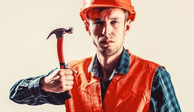 Konstruktor człowiek na białym tle. uderzenie młotkiem. konstruktor w kasku, młotek, złota rączka, budowniczowie w kasku. mężczyzna pracownik z brodą, kaskiem budowlanym, kaskiem