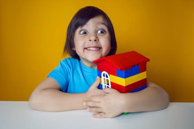 Konstruktor dziecko chłopiec w niebieskiej koszulce na żółtej ścianie buduje dom z kolorowych plastikowych kostek.