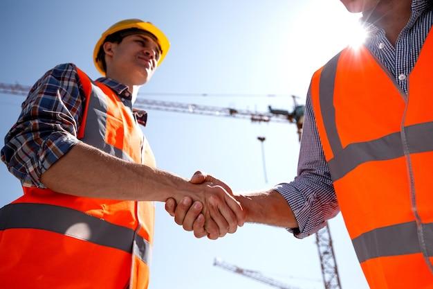 Konstruktor i architekt ubrany w pomarańczowe kamizelki robocze i hełmy ściskają sobie ręce na placu budowy w pobliżu dźwigu. .