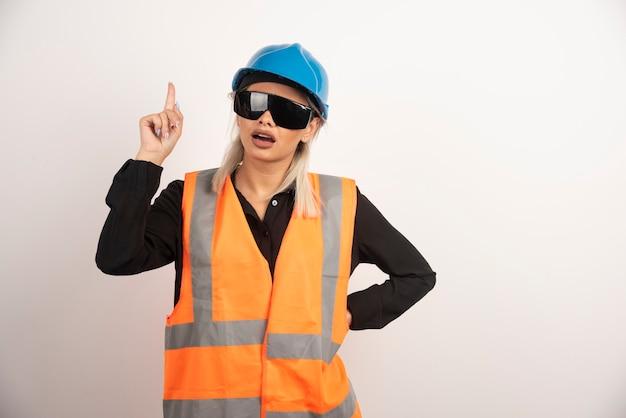 Konstruktor kobieta pokazując palec i pozowanie. wysokiej jakości zdjęcie