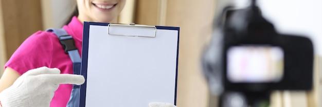 Konstruktor kobieta trzymająca dokumenty w rękach i nagrywająca wideo w aparacie