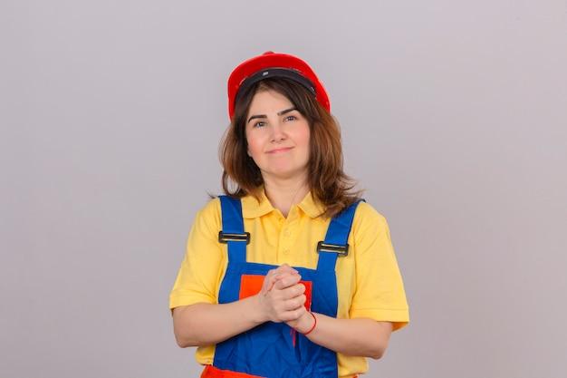 Konstruktor kobieta ubrana w mundur budowlany i kask ochronny, patrząc pewnie w kamerę, uśmiechnięty, trzymając się za ręce razem, myśląc pozytywnie na odizolowanej białej ścianie