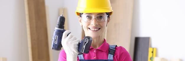 Konstruktor kobieta w kombinezonie i hełmie ochronnym, trzymając wiertło w rękach w warsztacie. męskie zawody dla koncepcji kobiet