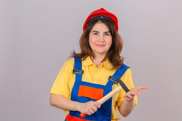 Konstruktor kobieta w mundurze budowlanym i kasku ochronnym z uśmiechem trzymając młotek w rękach stojących nad izolowaną białą ścianą