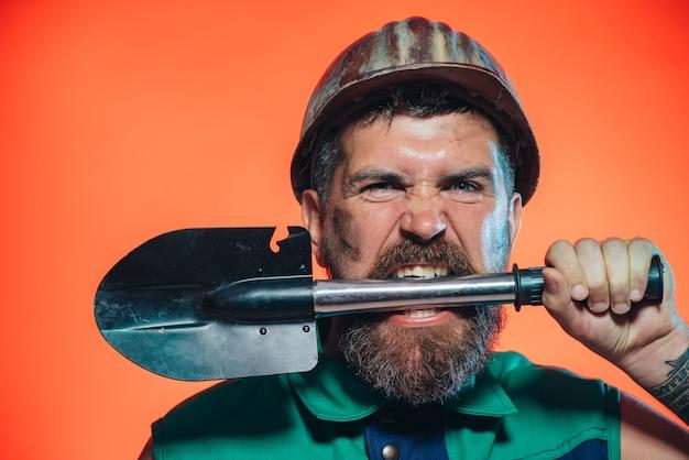 Konstruktor koncepcji budowy i górnictwa lub górnik nosi hełm i trzyma łopatę w zębach mężczyzna z