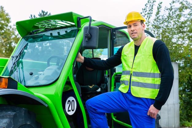 Konstruktor lub kierowca stojący przed maszynami budowlanymi na placu budowy