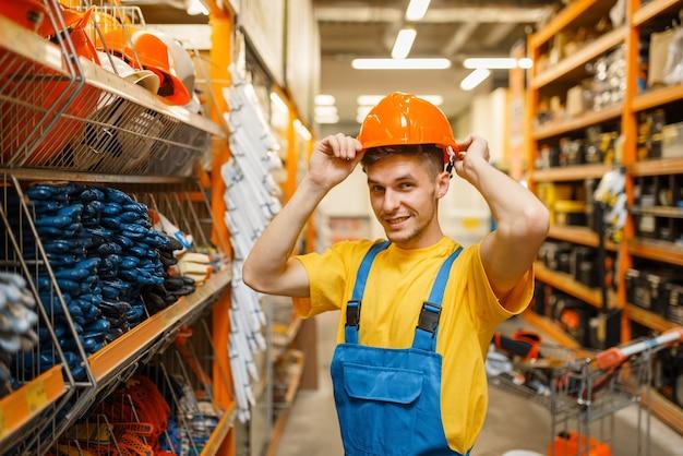 Konstruktor mężczyzna przymierzający kask na półce w sklepie z narzędziami. konstruktor w mundurze obejrzyj towary w sklepie dla majsterkowiczów