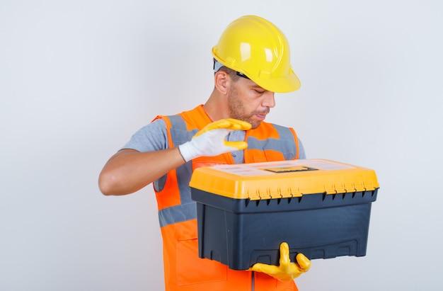 Konstruktor mężczyzna trzyma plastikową skrzynkę na narzędzia w mundurze, kasku, rękawiczkach, widok z przodu.