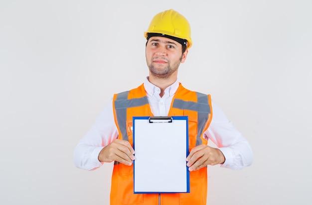 Konstruktor mężczyzna trzyma schowek i uśmiecha się w koszuli, jednolity, widok z przodu.