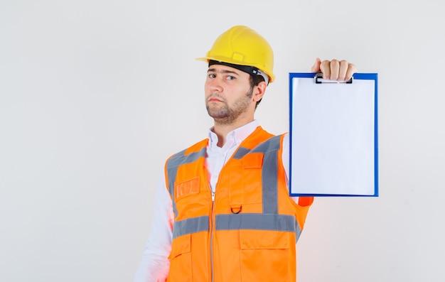 Konstruktor mężczyzna trzyma schowek w koszuli, mundurze i wygląda poważnie, widok z przodu.