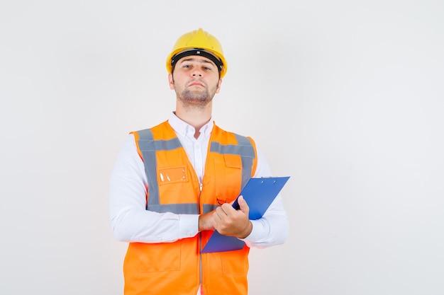 Konstruktor mężczyzna trzyma schowek w koszuli, mundurze i wygląda surowo, widok z przodu.