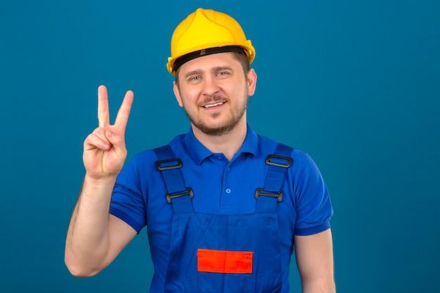 Konstruktor mężczyzna ubrany w mundur budowlany i hełm ochronny pokazujący numer dwa z palcami patrząc na bok uśmiechnięty przyjacielski stojący nad odizolowaną niebieską ścianą
