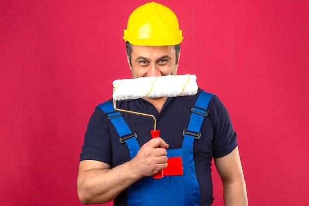 Konstruktor mężczyzna ubrany w mundur budowlany i kask ochronny stojący z wałkiem do malowania, uśmiechając się przebiegle nad izolowanym nad izolowaną różową ścianą