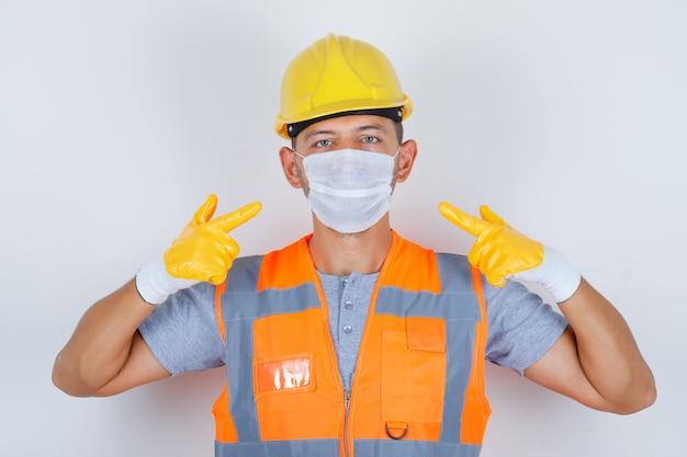 Konstruktor mężczyzna wskazując jego maskę medyczną w mundurze, hełmie, rękawiczkach, widok z przodu