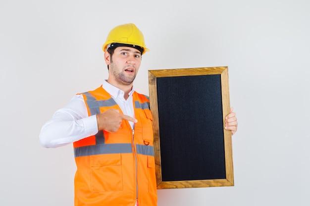 Konstruktor mężczyzna wskazując palcem na tablicy w koszuli, mundurze. przedni widok.